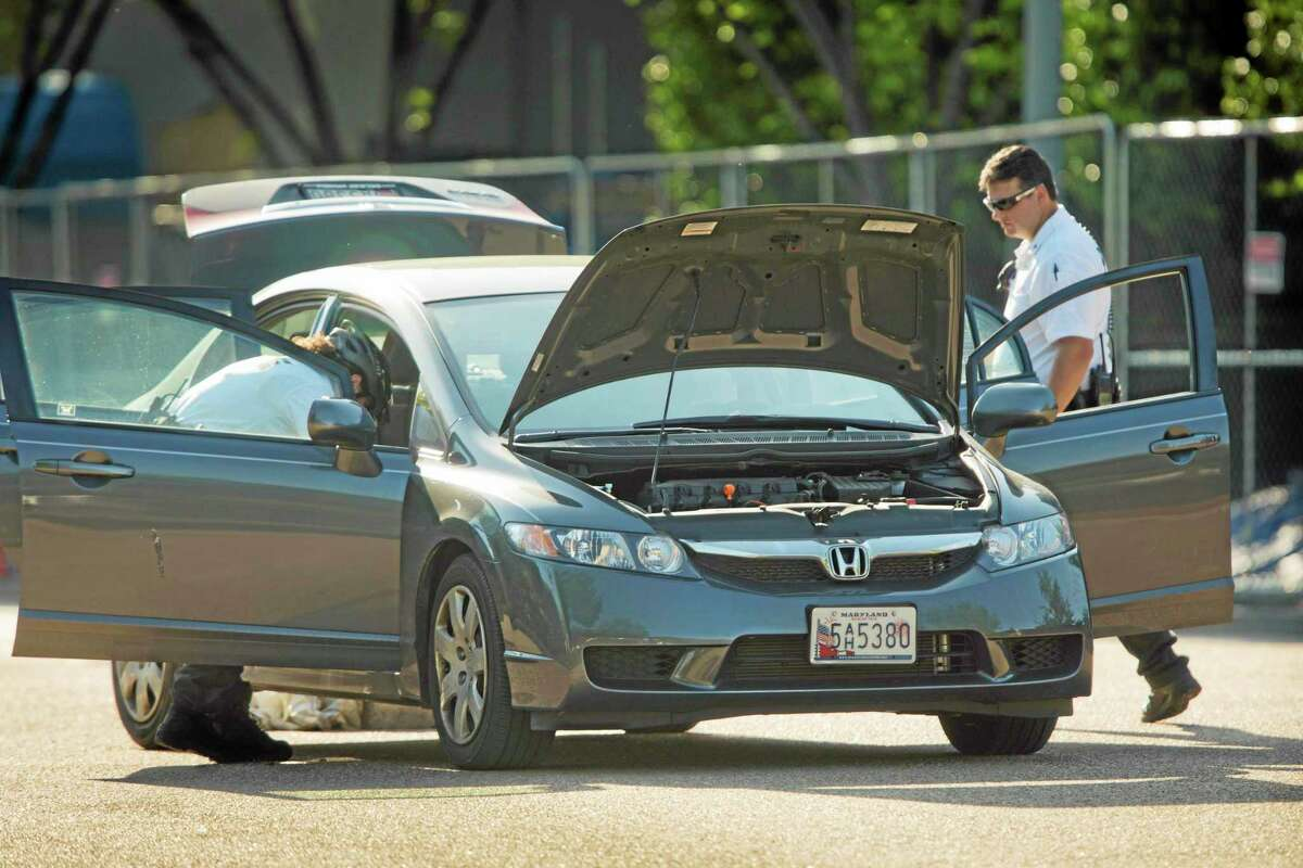 Uniformed Secret Service police officers search a vehicle after it followed a motorcade through a barrier on Pennsylvania Avenue near the front of the White House, Tuesday, May 6, 2014, in Washington. The Secret Service says access to the White House was halted for about an hour and a man is in custody after the incident. A law enforcement official says the motorcade was returning President Barack Obama's daughters to the White House. (AP Photo/Pablo Martinez Monsivais)