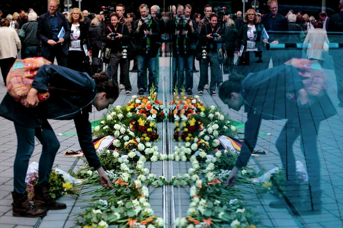 A woman lays down flowers at the new monument for the victims of euthanasia, as she is mirrored by the blue glass pane. in Berlin, Tuesday, Sept. 2, 2014. Germany has inaugurated the memorial to more than 200,000 people with physical and mental disabilities who were killed by the Nazis, who deemed their lives ìworthless. The 24-meter (79-foot) blue glass pane stands on the site of a villa where the mass murder of patients at hospitals and mental institutes was coordinated starting in 1940. The euthanasia programís methods included using gas chambers. (AP Photo/Markus Schreiber)