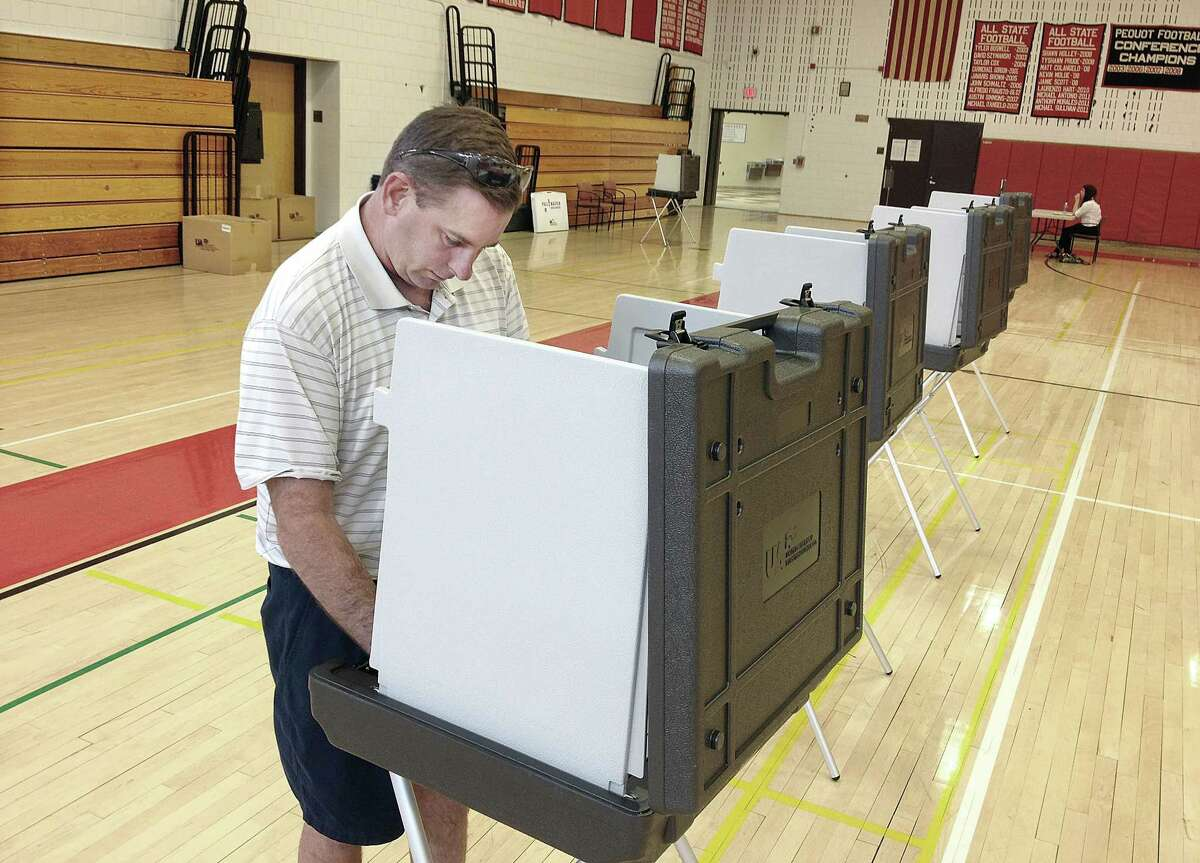 Catherine Avalone - The Middletown Press Cromwell resident Brian Michaud votes on the 2014-15 municipal budget in a referendum Tuesday at Cromwell High School.