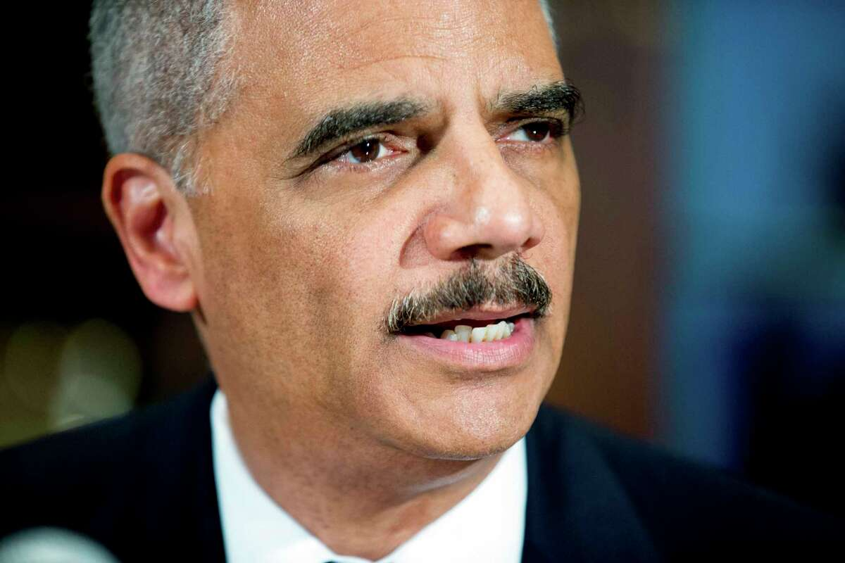 In this March 12, 2015, file photo, Attorney General Eric Holder announces six pilot cities for the National Initiative for Building Community Trust and Justice, at the Department of Justice in Washington. Holder said Wednesday, Oct. 28, that he disagrees with comments from FBI Director James Comey that suggested a connection between changes in police behavior and the homicide spike experienced by major American cities. Also in late October 2015, Holder questioned the constitutionality of a Connecticut law establishing a process for a possible new tribal casino.