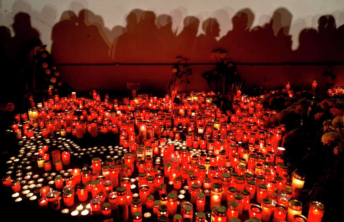 People cast shadows on a wall as they wait to light candles and lay flowers outside the compound that housed the nightclub where a fire occurred in the early morning hours in Bucharest, Romania, Saturday, Oct. 31, 2015. Hundreds of young people had gone clubbing at the hip Colectiv nightclub Friday night to enjoy a free concert by the Goodbye to Gravity metal band but the evening ended in horror, as the inferno caused a panic that killed tens of people and injured many others.