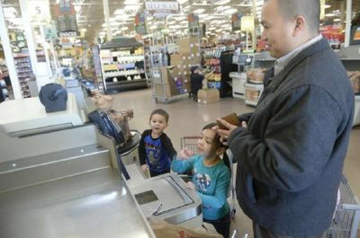 Paolo Diaz mixes a teachable moment with a fun outing to the grocery store with his daughter Maile, 6, and son Elijah, 3.