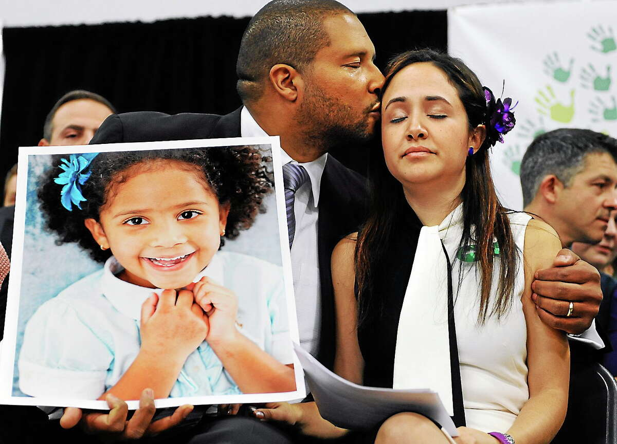 In this Jan. 14, 2014 photo, Jimmy Greene, left, kisses his wife Nelba Marquez-Greene as he holds a portrait of their daughter, Sandy Hook School shooting victim Ana Marquez-Greene, at a news conference at Edmond Town Hall in Newtown, Conn.