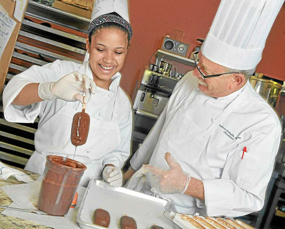 Chocolatier Roberto Lucheme teaches Zahria McDaniel, 14 how to dip the Mighty Moussicles Friday afternoon at Tschudin Chocolates & Confections on Main Street in Middletown. Lucheme won a year's supply of Hammond's Candy Canes and the title of 'Rewrapped' champion on the Food Network recently. Photo: File Photo  / TheMiddletownPress