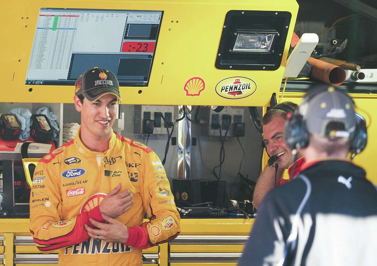 Joey Logano, left, reacts after winning the pole on Friday for Sunday's Sprint Cup race at Martinsville Speedway in Martinsville, Va.