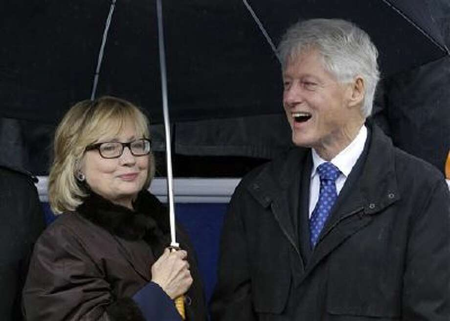 Former Secretary of State Hillary Rodham Clinton, left, and former President Bill Clinton try to stay dry Saturday under an umbrella as rain falls during inaugural ceremonies for Virginia Gov. Terry McAuliffe at the Capitol in Richmond, Va. Photo: AP / AP