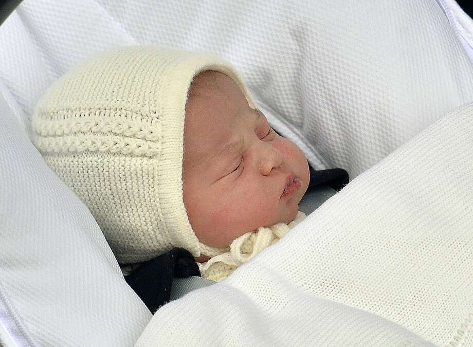 The newborn baby princess, born to parents Kate Duchess of Cambridge and Prince William, is carried in a car seat by her father from St. Mary's Hospital in London Saturday. Photo: Associated Press  / POOL PA