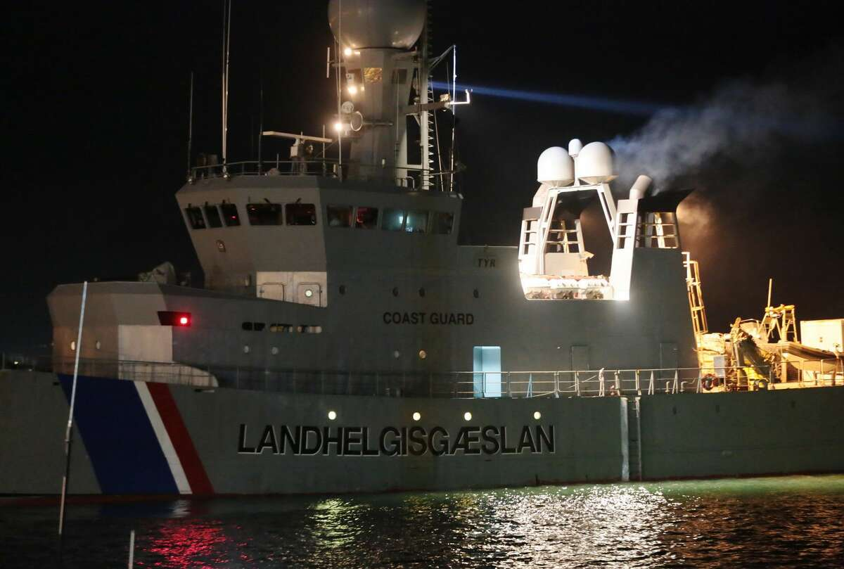 The Icelandic Coast Guard tows the cargo ship Ezadeen, carrying hundreds of migrants, as that arrives at the southern Italian port of Corigliano, Italy, Saturday, Jan. 3, 2015. The cargo ship was stopped with about 450 migrants aboard after smugglers sent it speeding toward the coast in rough seas with no one in command. Italian authorities lowered engineers and electricians onto the wave-tossed ship by helicopter to secure it, and the Icelandic Coast Guard towed it to the Italian port of Corigliano late Friday night. Smugglers who bring migrants to Europe by sea appear to have adopted a new, more dangerous tactic: cramming hundreds of them onto a large cargo ship, setting it on an automated course to crash into the coast, and then abandoning the helm. (AP Photo/Antonino D'Urso)