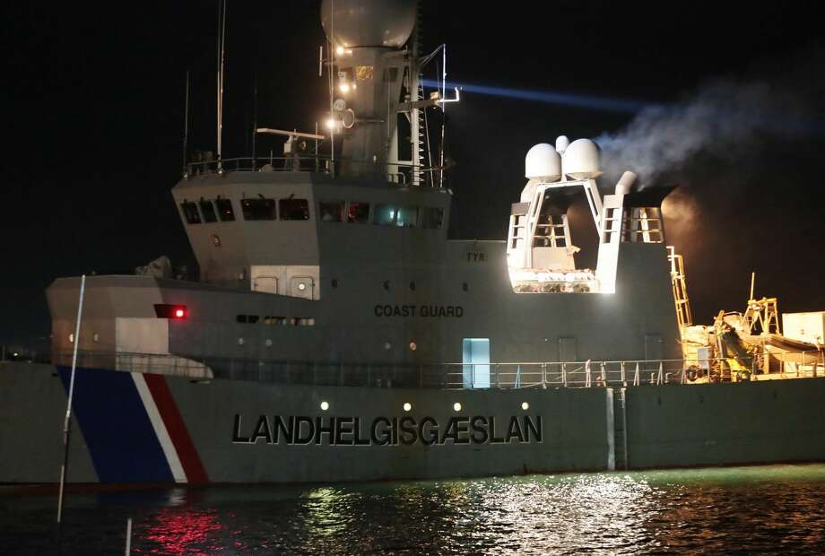 The Icelandic Coast Guard tows the cargo ship Ezadeen, carrying hundreds of migrants, as that arrives at the southern Italian port of Corigliano, Italy, Saturday, Jan. 3, 2015. The cargo ship was stopped with about 450 migrants aboard after smugglers sent it speeding toward the coast in rough seas with no one in command. Italian authorities lowered engineers and electricians onto the wave-tossed ship by helicopter to secure it, and the Icelandic Coast Guard towed it to the Italian port of Corigliano late Friday night. Smugglers who bring migrants to Europe by sea appear to have adopted a new, more dangerous tactic: cramming hundreds of them onto a large cargo ship, setting it on an automated course to crash into the coast, and then abandoning the helm. (AP Photo/Antonino D'Urso) Photo: AP / AP