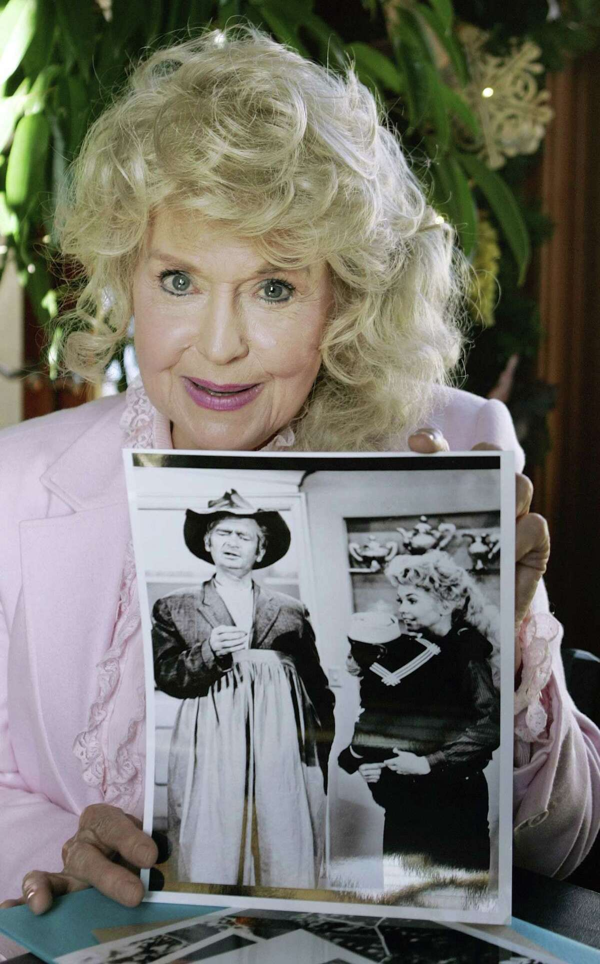 """FILE - In this Jan. 8, 2009 file photo, Donna Douglas, who starred in the television series """"The Beverly Hillbillies"""" holds a publicity picture of herself from the show, in Baton Rouge, La. Douglas, who played the buxom tomboy Elly May Clampett on the hit 1960s sitcom has died. Douglas, who was 82, died Thursday, Jan. 1, 2015, in Baton Rouge, where she lived, her niece, Charlene Smith, said. (AP Photo/Bill Haber, File)"""