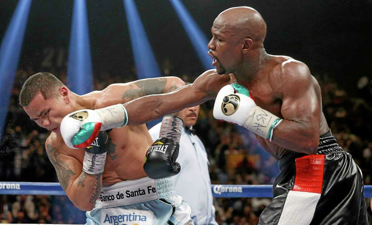 Floyd Mayweather Jr., right, connects with a right to the head of Marcos Maidana, from Argentina, in their WBC-WBA welterweight title boxing fight Saturday in Las Vegas.