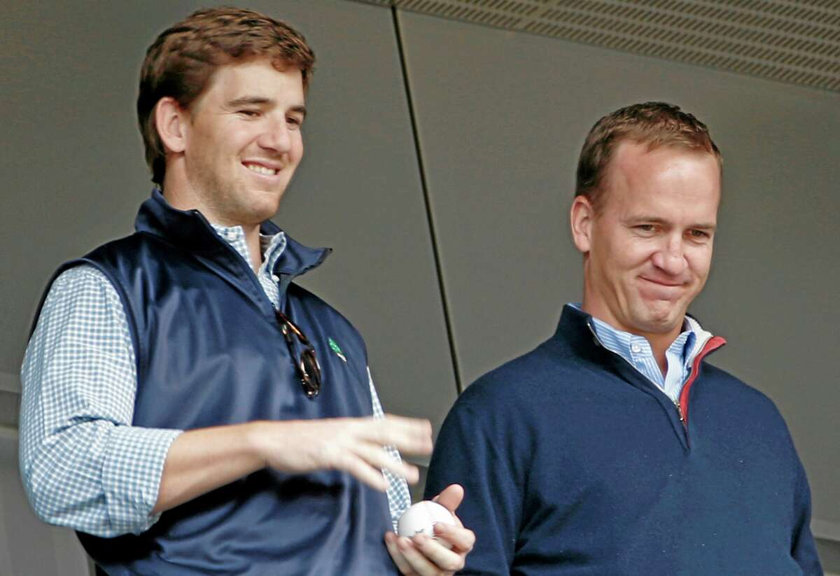 Broncos quarterback Peyton Manning, right, and his brother, Giants quarterback Eli Manning, watch from New York Yankees' Derek Jeter's suite during Sunday's game between the Yankees and the Tampa Bay Rays at Yankee Stadium.