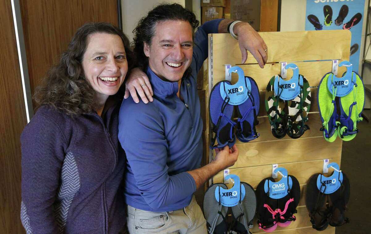 Husband and wife team and cofounders of Xero Shoes, Lena Phoenix and Steven Sashen, stand with a display of a few examples of their company's sandals, as they move into their newer, larger headquarters in Broomfield, Colorado. The two hope for an easier time getting a Small Business Administration loan in the new year. The application and approval process they went through for a $500,000 loan in 2014 took eight months, longer than the two months their lender initially forecast.