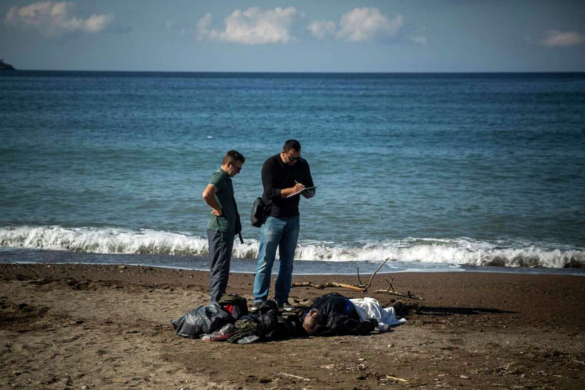 Police officers take notes over the body of a dead man in Petra village on the northeastern Greek island of Lesbos, Friday, Oct. 30, 2015. The deaths occurred amid a surge of crossings to Greek islands involving migrants and refugees from Syria, Afghanistan and other countries ahead of winter and as European governments weighed taking tougher measures to try and limit the number of arrivals in Europe.