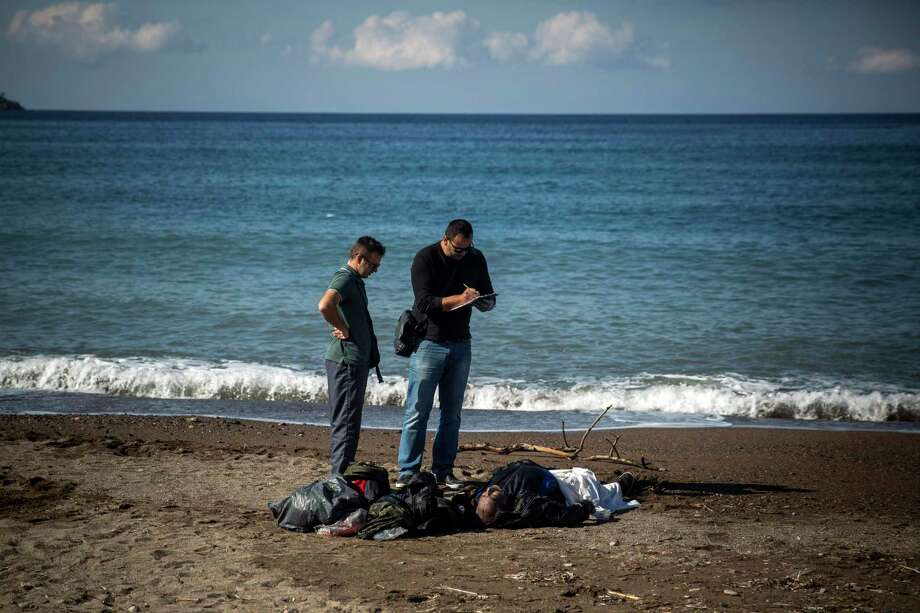 Police officers take notes over the body of a dead man in Petra village on the northeastern Greek island of Lesbos, Friday, Oct. 30, 2015. The deaths occurred amid a surge of crossings to Greek islands involving migrants and refugees from Syria, Afghanistan and other countries ahead of winter and as European governments weighed taking tougher measures to try and limit the number of arrivals in Europe. Photo: AP Photo/Santi Palacios   / AP