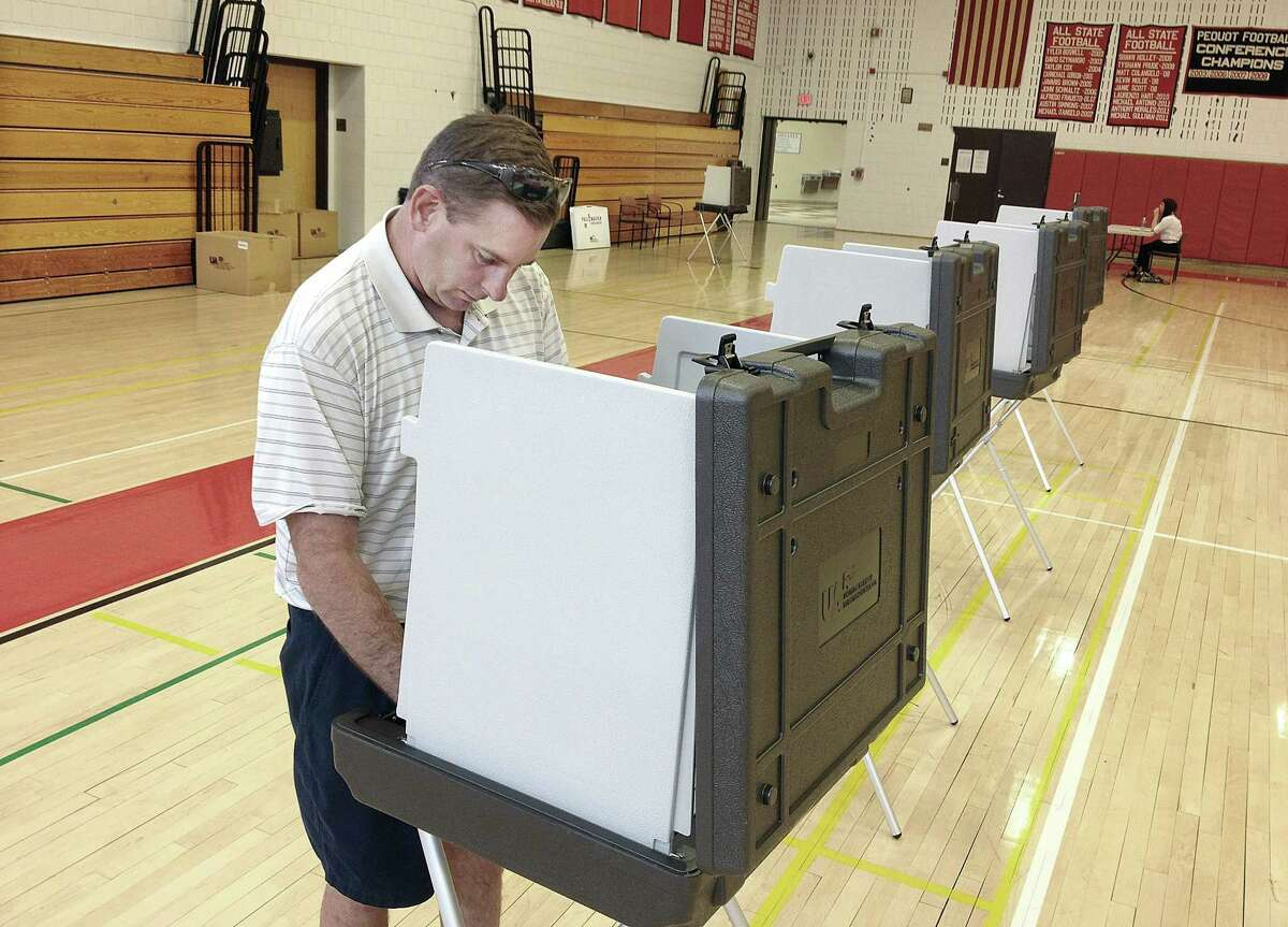 Cromwell resident Brian Michaud votes on the 2014-15 municipal budget in a referendum at Cromwell High School in this Press archives photo.