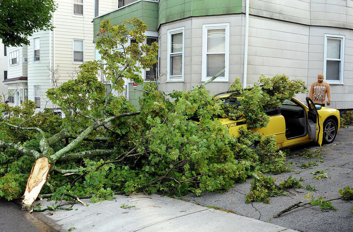 """Angel Alcoba looks at the damage to his 2007 Dodge Charger in his driveway on Windham Street, Monday, Sept. 1, 2014, in Worcester, Mass. A tree limb smashed through the back window of the car during Sunday night's storm. """"I thought the whole house was coming apart,"""" Alcoba said about the storm. The National Weather Service confirmed that Sunday night's storm in the Grafton Hill and Vernon Hill neighborhoods was a tornado. (AP Photo/Worcester Telegram & Gazette, Rick Cinclair)"""