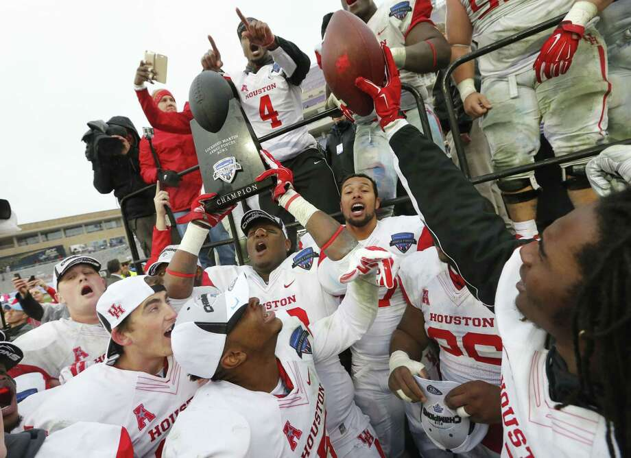 Houston players celebrate with the trophy after they defeated Pittsburgh 35-34 in the Armed Forces Bowl on Friday in Fort Worth, Texas. Photo: Sharon Ellman — The Associated Press  / FR170032 AP