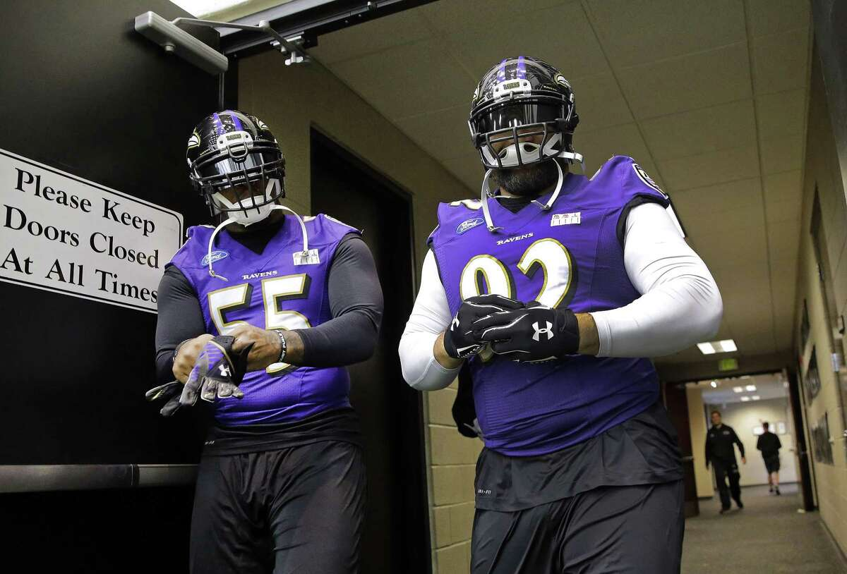 Baltimore Ravens linebacker Terrell Suggs, left, and defensive end Haloti Ngata walk to practice on Tuesday in Owings Mills, Md.