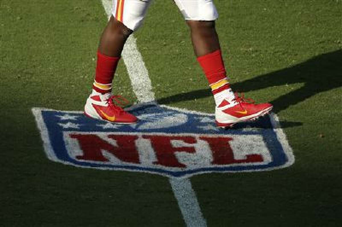 A player for the Kansas City Chiefs walks across an NFL logo before a preseason NFL football game against the San Francisco 49ers Friday, Aug. 16, 2013, in Kansas City, Mo. (AP Photo/Charlie Riedel)
