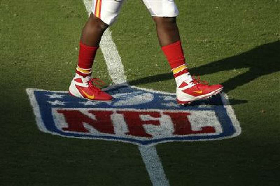 A player for the Kansas City Chiefs walks across an NFL logo before a preseason NFL football game against the San Francisco 49ers Friday, Aug. 16, 2013, in Kansas City, Mo. (AP Photo/Charlie Riedel) Photo: AP / AP