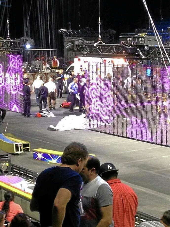 """In a cell phone photo provided by Tara Griggs, emergency workers tend to injured performers after a platform collapsed, Sunday, May 4, 2014, during the Ringling Brothers and Barnum and Bailey Circus' Legends show at the Dunkin' Donuts Center in Providence, R.I. At least nine people were injured in the fall, including a dancer below. Roman Garcia, general manager of the show, said the accident occurred during the """"hair hang"""" act in which the performers hang from their hair. Photo: (AP Photo - Tara Griggs)"""