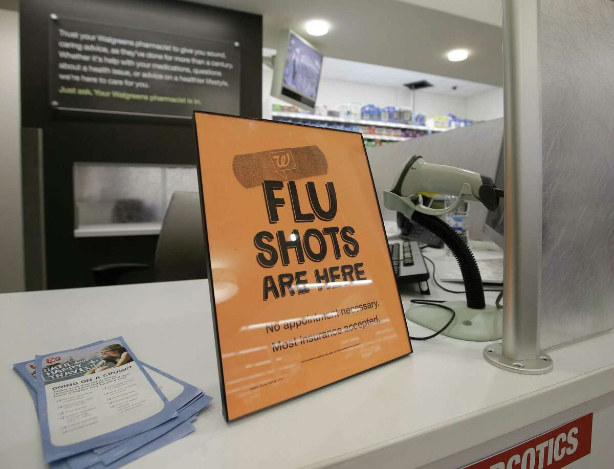 FILE - In this Sept. 16, 2014 file photo, a sign lets customers know they can get a flu shot at a Walgreen store in Indiana.