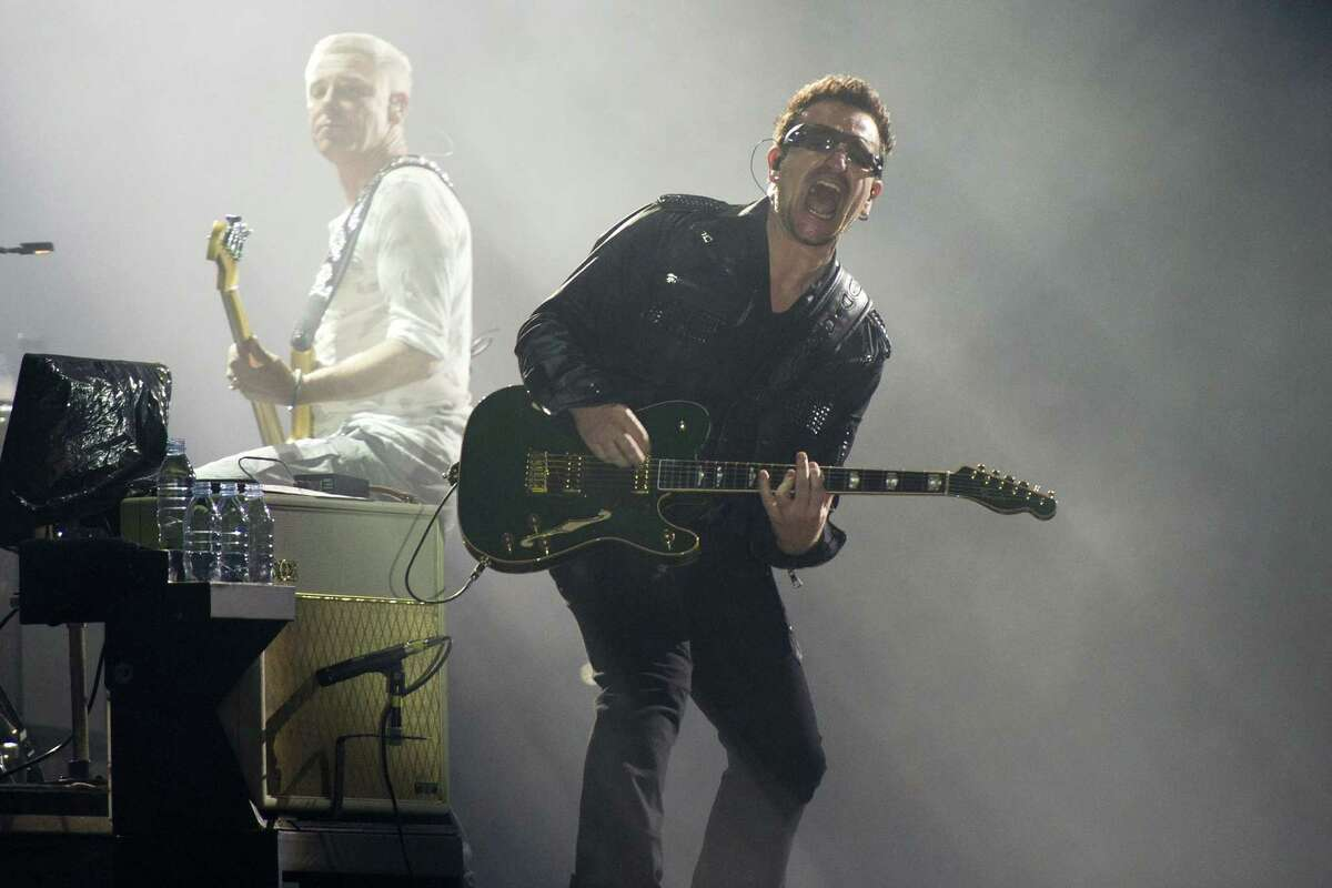 FILE - In this July 20, 2011 file photo, Bono, right, and Adam Clayton, from the rock group U2, perform in concert as part of U2ís 360 Tour at the New Meadowlands Stadium in East Rutherford, N.J. Bono wrote on the band's website Thursday Jan. 1, 2015, he may never play guitar again due to injuries suffered in a New York City cycling accident in November. (AP Photo/Charles Sykes, file)
