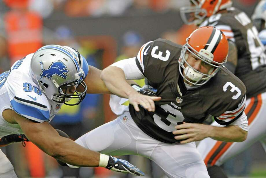 "FILE - In this Oct. 13, 2013, file photo, Cleveland Browns quarterback Brandon Weeden (3) is hit by Detroit Lions defensive tackle Ndamukong Suh after throwing a pass in the first quarter of an NFL football game in Cleveland. The league is reviewing Suh's play against Cleveland.  The hit, which wasn't penalized, was shown on a video posted on NFL.com on Tuesday, Oct. 15, 2013, as vice president of officiating Dean Blandino said, ""Why don't we look at it some more?"" in the league's officiating command center. (AP Photo/David Richard, File) Photo: AP / FR25496 AP"