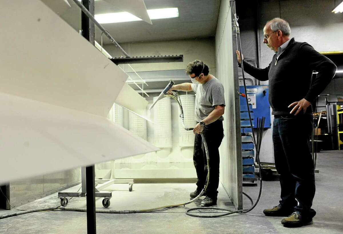 In this Thursday, May 1, 2014 photo, Lou Tashash, owner and president of R-D Manufacturing Inc., left, watches painter Francisco Mirlas powder-coat metal at his precision sheet manufacturing business in East Lyme, Conn. Tashash, who employs 14 workers, is lobbying legislators to kill a measure to establish a state-run pension plan, which he sees as a burdensome mandate. Lawmakers in Connecticut and other states are responding to a widespread loss of private-sector pensions, a lack of access to employer-sponsored retirement accounts in smaller businesses and stagnant incomes that make it hard for workers to contribute to their own retirement plan or company account. (AP Photo/Jessica Hill)