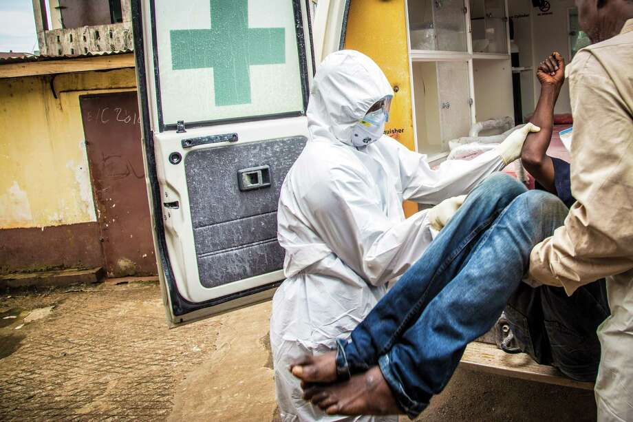 FILE- In this Wednesday, Sept. 24, 2014 file photo, health workers load a suspected Ebola patient into the back of an ambulance in Freetown, Sierra Leone. Professors from three leading British universities say policies favoring international debt repayment over social spending contributed to the Ebola crisis by hampering health care in the three worst-hit West African countries. Conditions for loans from the International Monetary Fund prevented an effective response to the outbreak that has killed nearly 8,000 people, the academics allege in a report in The Lancet Global Health journal this month. (AP Photo/Michael Duff, File) Photo: AP / AP