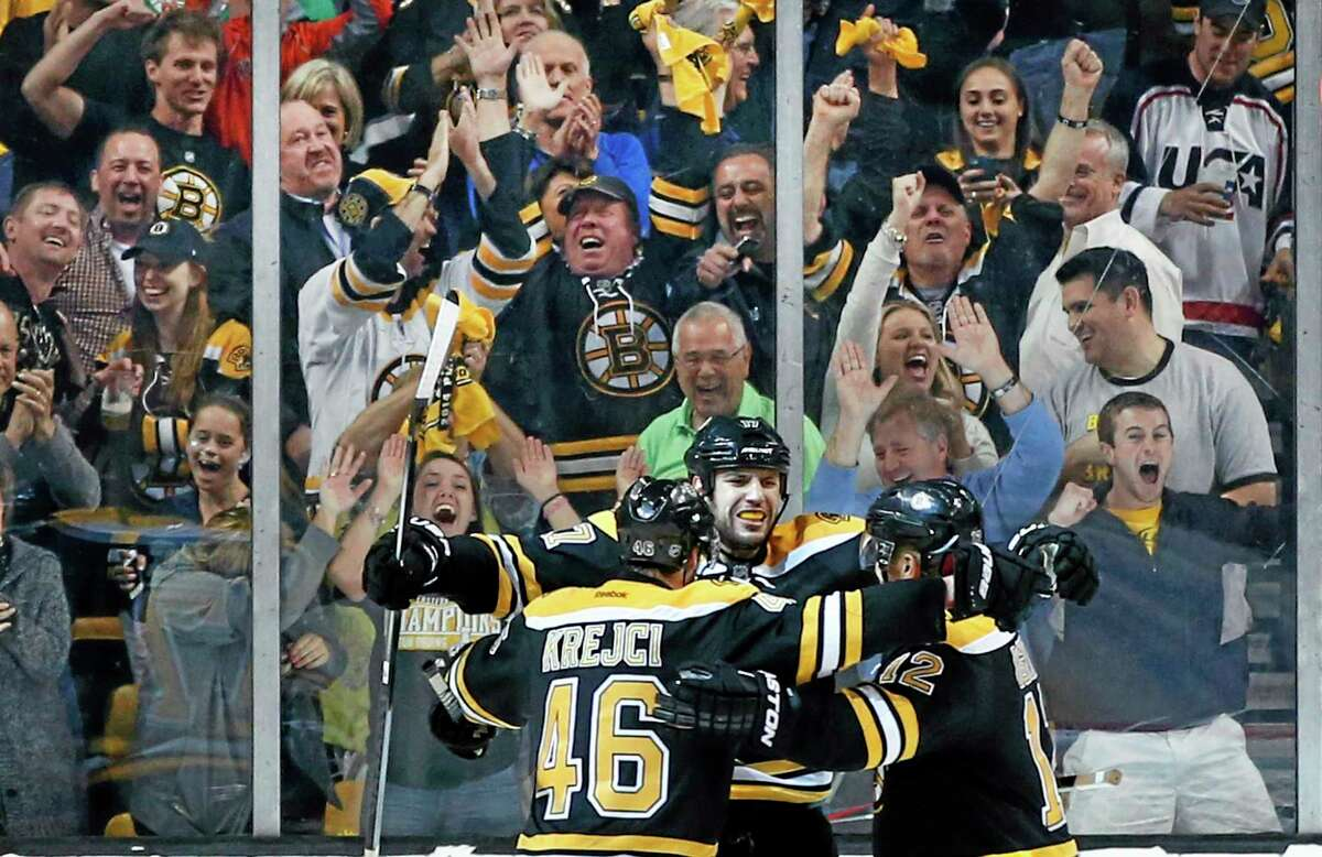 Fans cheer as Bruins left wing Milan Lucic, center, celebrates his empty-net goal with center David Krejci (46) and right wing Jarome Iginla, right, late in the third period in Game 2 of a second-round Stanley Cup series against the Montreal Canadiens on Saturday in Boston.