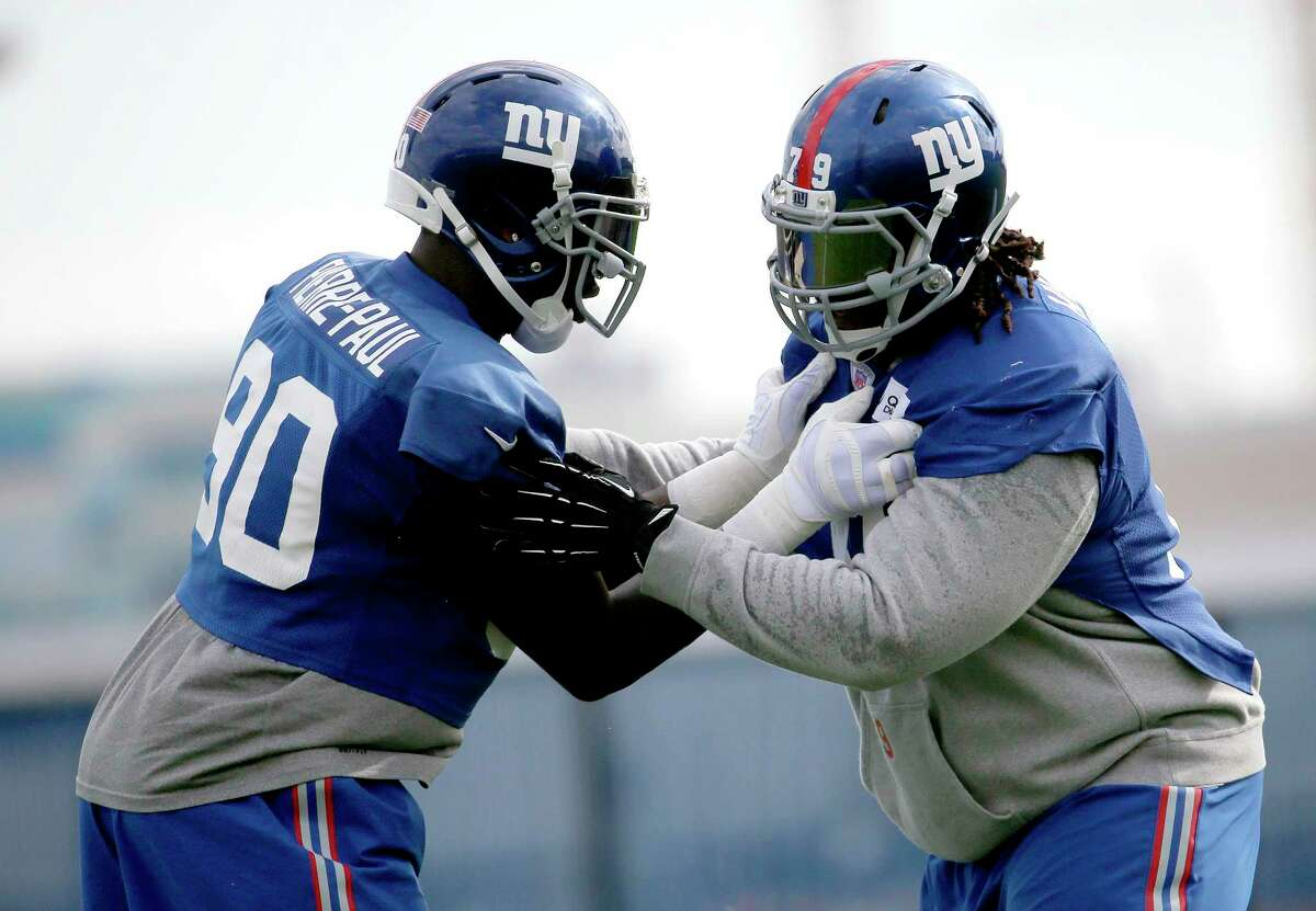 Giants defensive end Jason Pierre-Paul, left, grabs at defensive tackle Montori Hughes during practice Thursday in East Rutherford, N.J.