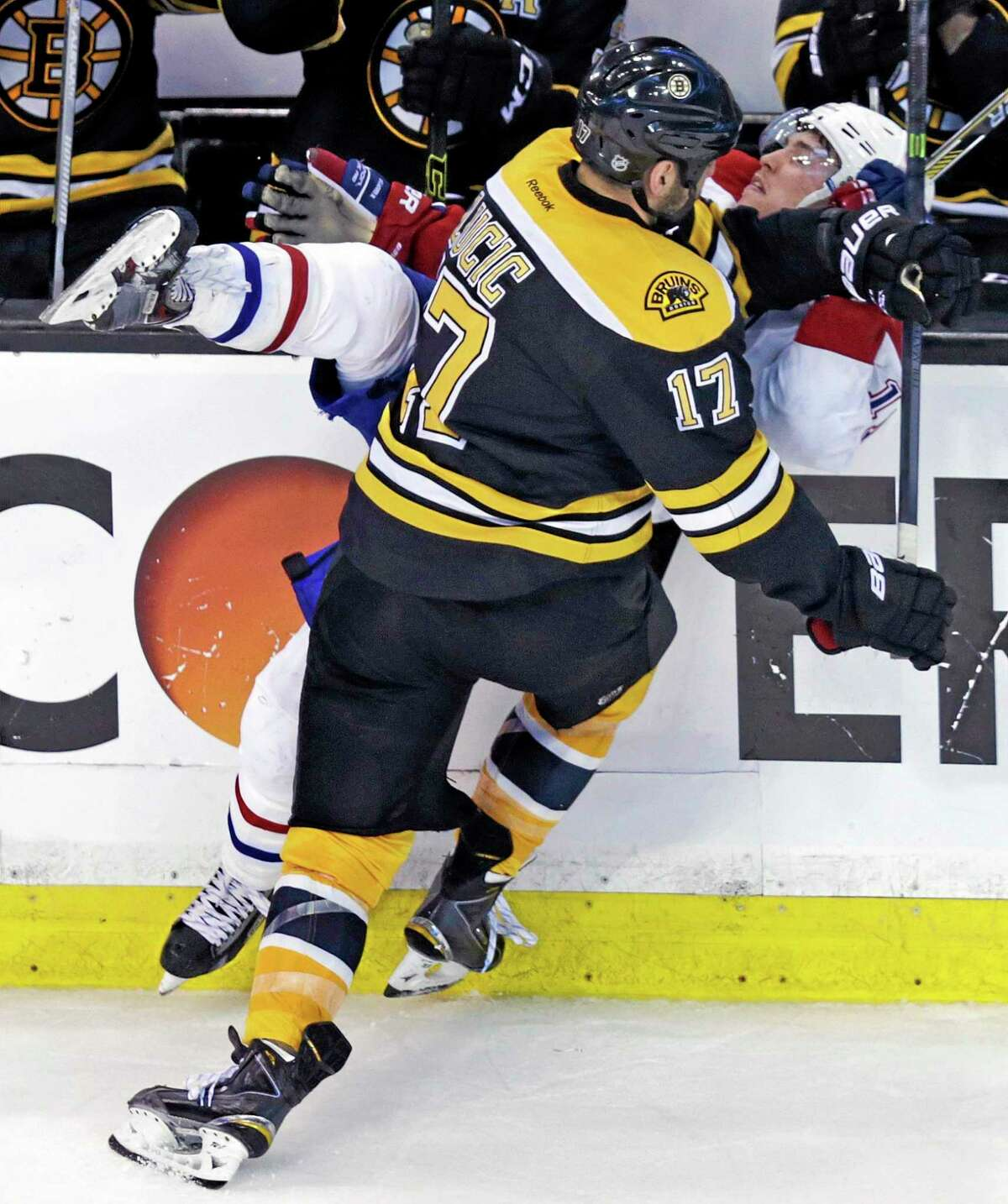 Bruins left wing Milan Lucic (17) drives Montreal Canadiens right wing Brendan Gallagher (11) into the board during the third period of Game 2 in the second-round Stanley Cup series on Saturday in Boston.