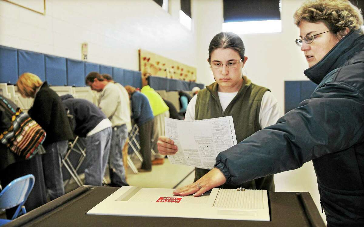 Middletown resident Valerie LeMontagne explains how to cast a ballot to her daughter, Rachel LeMontagne, who was voting in her first election at Farm Hill School in Middletown in this file photo.