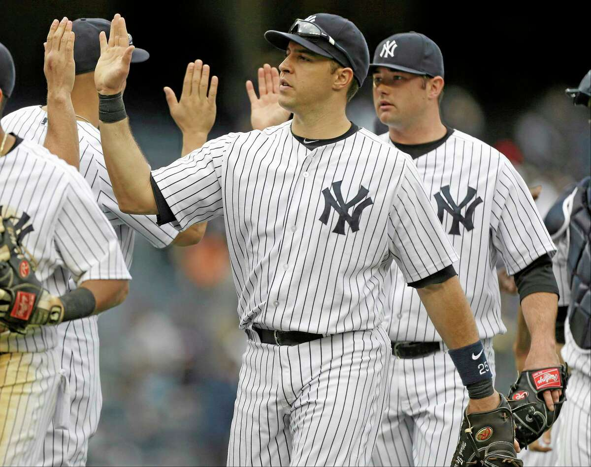 Mark Teixeira celebrates with his Yankee teammates after a 9-3 win over the Tampa Bay Rays on Saturday in New York.