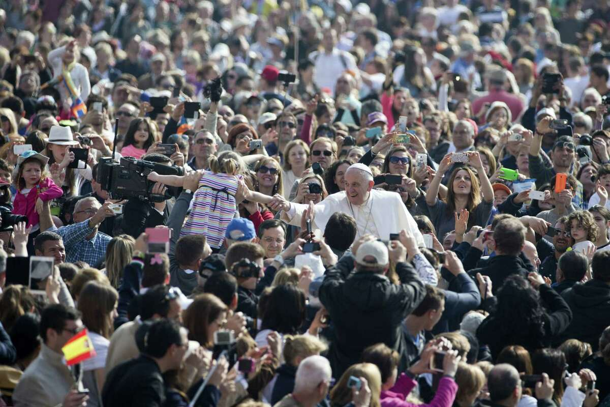 FILE - In this Wednesday, April 15, 2015 file photo, Pope Francis, center, greets a child as he arrives for his weekly general audience, in St. Peter's Square, at the Vatican. When Pope Francis visits the United States this fall, he can expect the same rock-star adulation that greets him wherever he goes. But his positions on hot-button issues such as the death penalty and climate change could quickly set the stage for conflict. That may explain why Francis has been clearing the decks on a host of less high-profile matters of contention that could also have marred the visit.