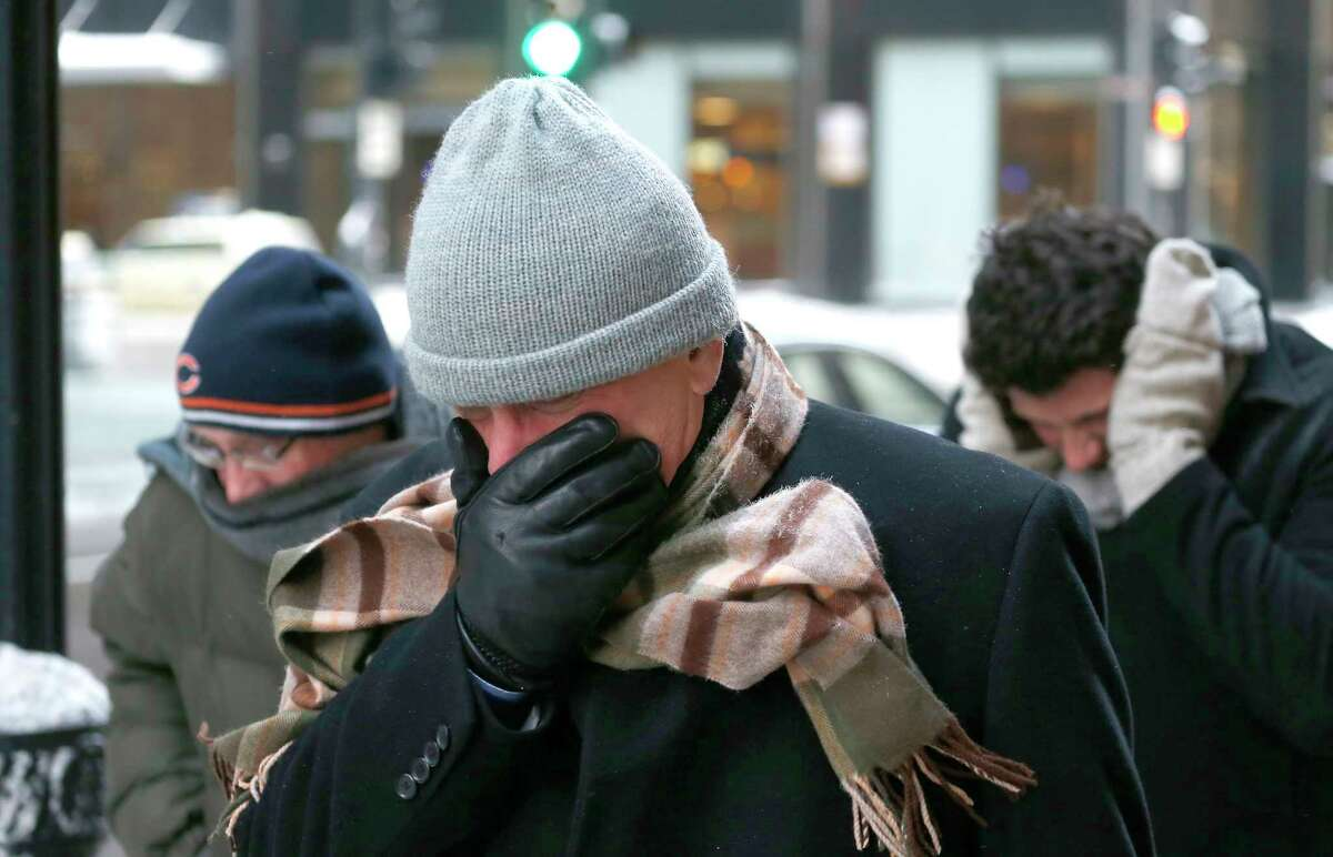 Three men protect themselves from the elements as they walk in Chicago's Loop with temperatures well below zero and wind chills expected to reach 40 to 50 below last January.