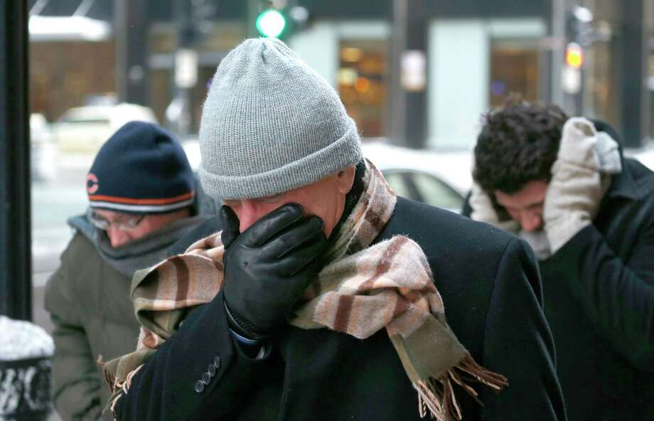 Three men protect themselves from the elements as they walk in Chicago's Loop with temperatures well below zero and wind chills expected to reach 40 to 50 below last January. Photo: File Photo  / AP