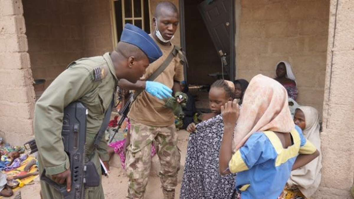In this photo made available by the Nigerian Military taken Wednesday, April 29, 2015, a Nigerian soldier speaks to woman and children that were allegedly rescued by the Nigerian Military after being taken by Islamic extremists in Sambisa Forest, Nigeria. Scores more women and children have been rescued from Islamic extremists in the remote Sambisa Forest, Nigeria's military said amid reports that some of the women fought their rescuers fiercely.