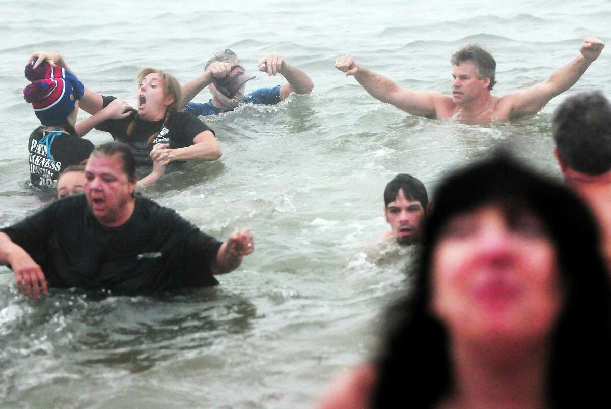 Participants react to the cold water as they participate in the 14th annual Icy Plunge for the Cure Saturday at the beach behind the Savin Rock Conference Center in West Haven.