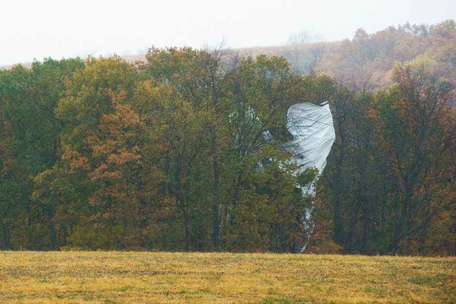 Part of what appears to be an unmanned Army surveillance blimp rests in the trees near Muncy, Pa., on Wednesday, Oct. 28, 2015. The 240-foot helium-filled unmanned Army surveillance blimp broke loose from its mooring in Maryland and floated over Pennsylvania for hours Wednesday with fighter jets on its tail, triggering blackouts across the countryside as it dragged its tether across power lines. Photo: Larry Deklinski/The News-Item Via AP   / The News-Item