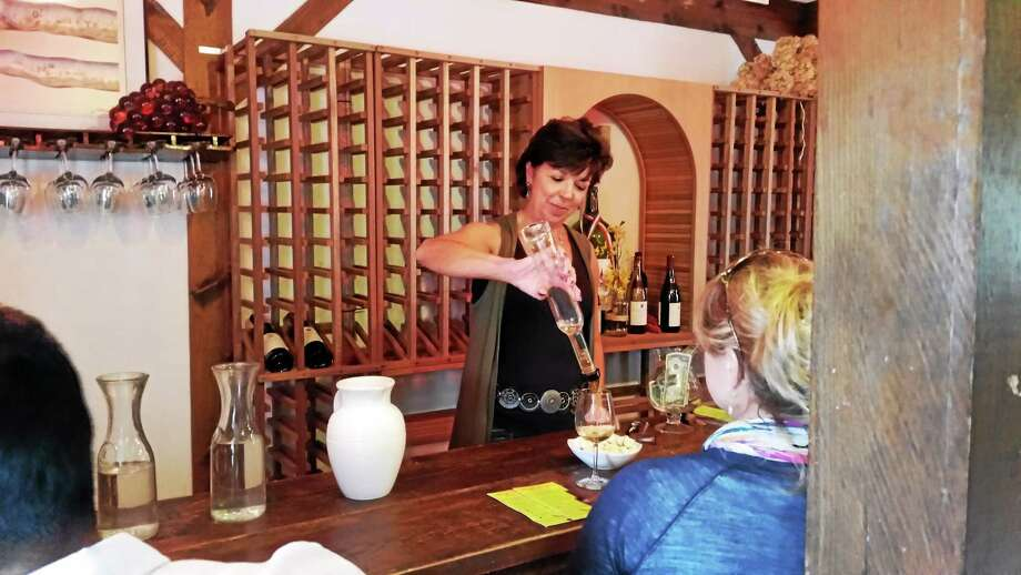 N.F. Ambery — Special to the Register Citizen Vineyard employee Susan Robinson serves wine during tastings at the Haight-Brown Vineyards in Litchfield at the Harvest Festival in September. Photo: Journal Register Co.