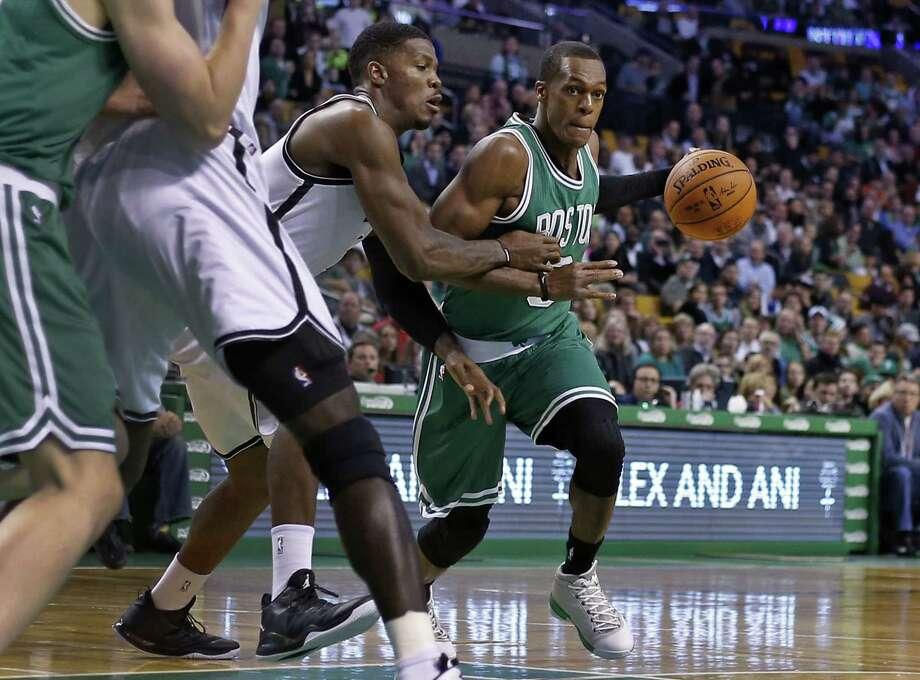 Boston Celtics guard Rajon Rondo dribbles against Brooklyn Nets guard Joe Johnson, left, in the first quarter of Wednesday's game in Boston. Photo: Elise Amendola — The Associated Press  / AP