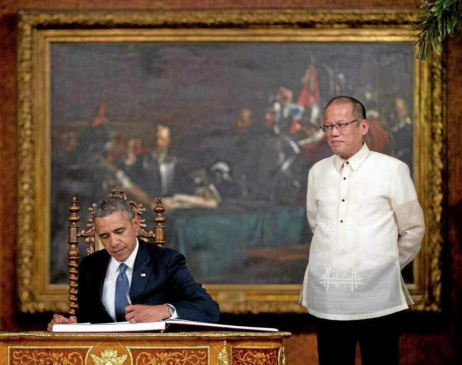 FILE - In this Monday, April 28, 2014 file photo, U.S. President Barack Obama signs a guestbook as Philippine President Benigno Aquino III looks on at the Malacanang Palace in Manila. A new defense pact that will allow thousands of U.S. troops to be temporarily based in Philippines for the first time in more than 20 years signals closer cooperation in the alliesí hot-and-cold relationship that has been shaped over the decades by war, terrorism and now, jitters over China's rise. The 10-year agreement, signed Monday as Obama arrived in Manila, was considered the centerpiece of his four-nation Asian trip, which he used to reassure allies like Japan and the Philippines of American military backing as they wrangle with China in increasingly tense territorial disputes. (AP Photo/Carolyn Kaster, File) Photo: AP / AP