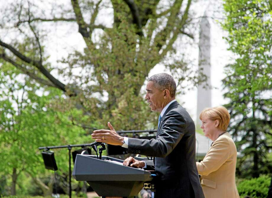 President Barack Obama gestures as he speaks during a joint news conference with German Chancellor Angela Merkel, Friday, May 2, 2014, in the Rose Garden of the White House in Washington. Obama and Merkel are putting on a display of trans-Atlantic unity against an assertive Russia, even as sanctions imposed by Western allies seem to be doing little to change Russian President Vladimir Putin's reasoning on Ukraine. (AP Photo/Carolyn Kaster) Photo: AP / AP