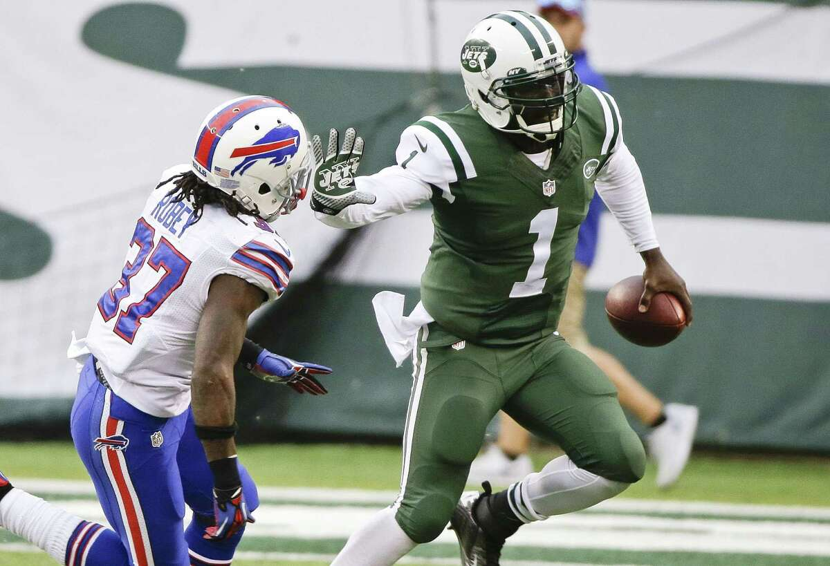 New York Jets quarterback Michael Vick (1) stiff arms the Buffalo Bills' Nickell Robey (37) during the second half of Sunday's game in East Rutherford N.J.