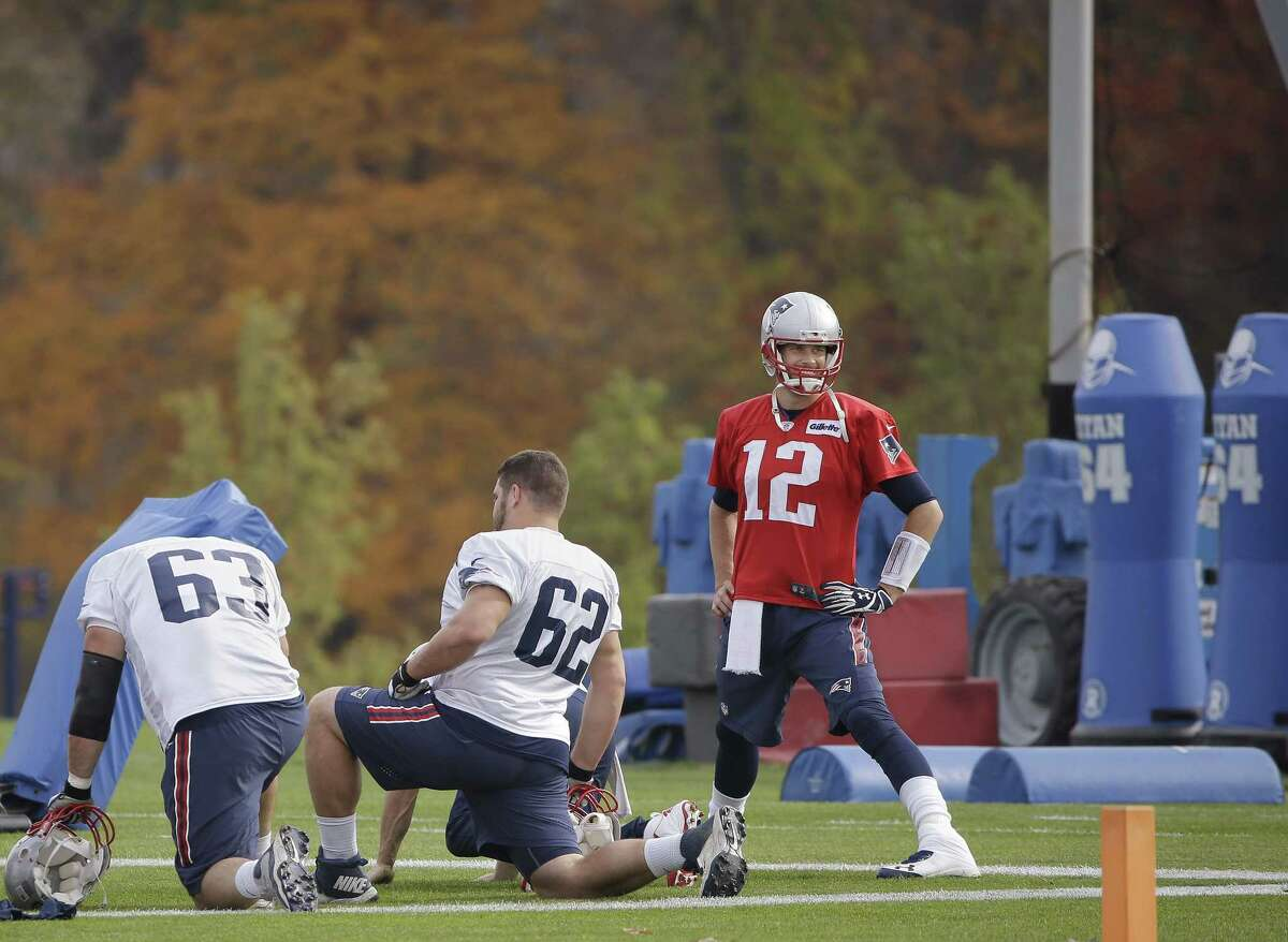 New England Patriots quarterback Tom Brady (12) stretches with offensive linemen Ryan Wendell (62) and Dan Connolly (63) before practice Wednesday in Foxborough, Mass.