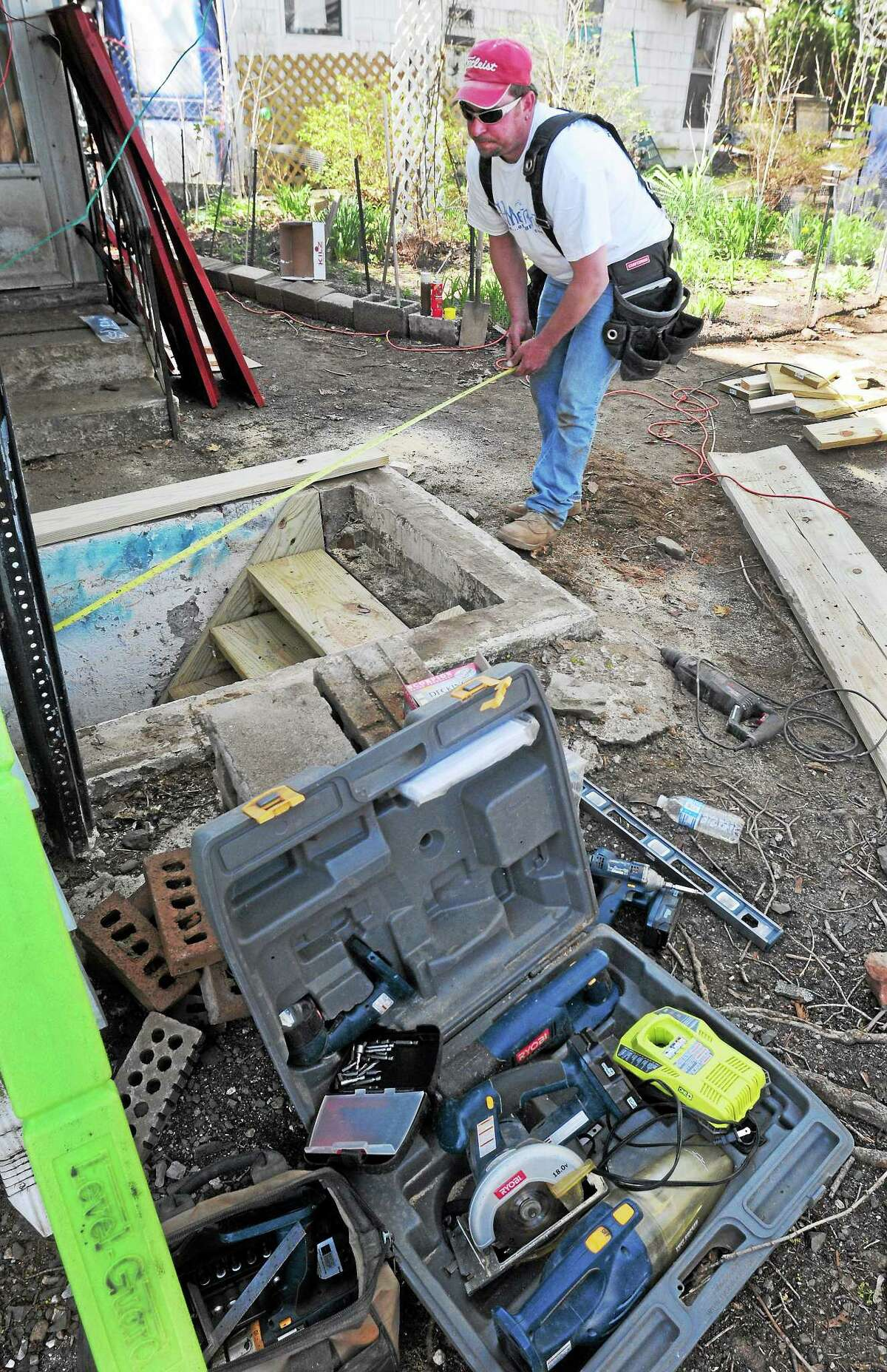 Union carpenter Ricy Bourgoin of Terryville, a HomeFront Inc. volunteer, measures a hatchway that he will repair Saturday at the Malewicki residence on Whitney Avenue in Milford.