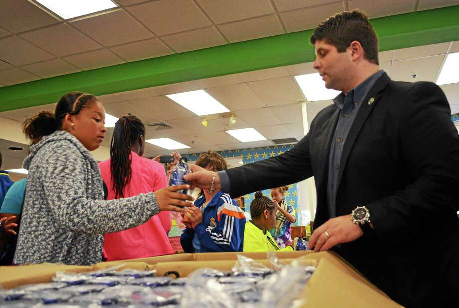 Mayor Dan Drew hands out the water bottles students designed Thursday at the WWMS library. Photo: Cassandra Day — The Middletown Press